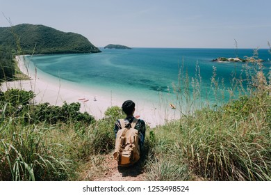 Backpack trave man Sitting on sea cliff . White sand beach with blue sea on Koh Samaesarn. Sattahip, Chonburi, Thailand