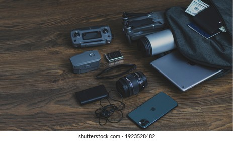 Backpack with travel gadgets, on a wooden background, top view. High-tech travel gadgets, phone, wallet, dollars, headphones, tablet, drone, camera, passport. Gomel Belarus - 16.02.2021
