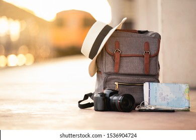 Backpack travel with hat, camera, map, earphone and smart phone on the ground of train station at sunset background train. travel and backpack concept. - Shutterstock ID 1536904724