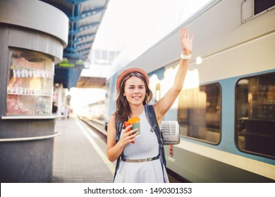 backpack traveler woman waving hand at train station platform summer holiday traveling concept. Female tourist greeting and enjoy on train, travel concept. Theme transportation and travel.