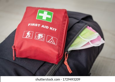 Backpack with   two face protection mask  and   first aid  kit  ready for couple  mountain trip .Measures to avoid crowded and contamination with covid -19 after leaving the quarantine period .