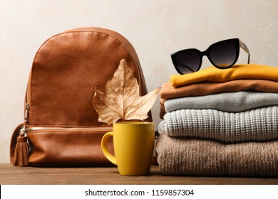Backpack and warm clothes on wooden table on neutral background. Concept autumn clothes.