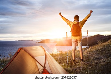 Backpacker with arms raised looking at beautiful sunrise at big lake near tent