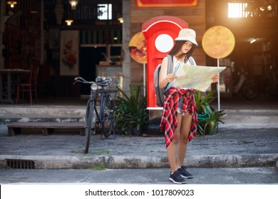 backpacker cute girl standing on street and looking at map near market and shop. blurred background, Traveler and holidays, Backpacker concept.
