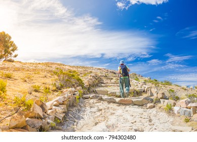 Backpacker explores Inca Trail on Island of the Sun, Titicaca Lake, scenic travel destination in Bolivia. Travel adventures and vacations in the Americas. Toned image, backlight, sun.