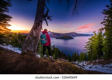 Backpacker Girl Looking at Crater Lake at Sunset Wizar Island and Watchman Peak in the Background