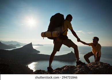 Backpacker helps to his friend to climb to rock