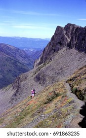 Backpacker hiker descends the trail on Norse Peak, Mount Rainier National Park, Washington