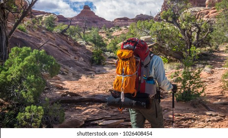 Backpacker hiker man treks through canyon cliff in canyonlands national park adventure southwest hiking backpacking strong strength vacation rugged southwest desert geology scenic landscape photo