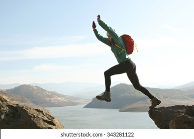 A backpacker jumping over a large gap on her hike