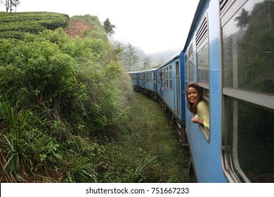 An backpacker leans out the window of the Blue Train from Kandy to Ella in the Sri Lankan mountain tea plantations