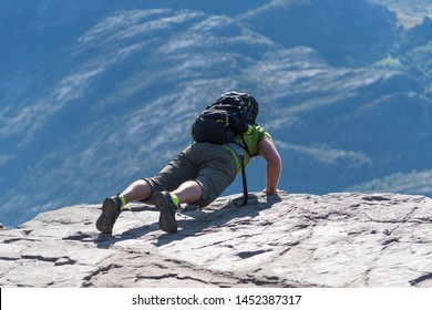 Backpacker looking carefully over the edge of Pulpit Rock. The Pulpit Rock or Preacher's Chair is a tourist attraction in the municipality of Forsand in Rogaland county