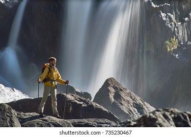 Backpacker looking at waterfall in beautiful summer nature landscape. Portrait of male adult back standing outdoor.