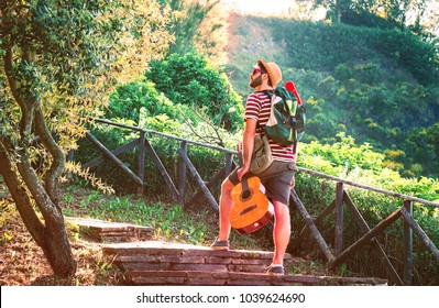 Backpacker man climbing stone stairs at mountain mediterranean park  - Traveler male trekking excursion day on green hill - Globe trotter reaching the peak rear view - Travel around the world concept