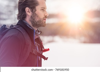 backpacker man detail wearing anorak jacket. exploring snowy land walking and skiing with alpine ski. Europe Alps. Winter sunny day, snow, wide shot, warm sun flare.travelling, side view