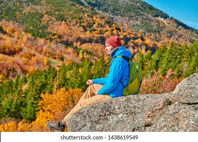 Backpacker man hiking at Artist's Bluff in autumn. Fall colours in Franconia Notch State Park. White Mountain National Forest, New Hampshire, USA
