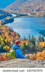 Backpacker man hiking at Artist's Bluff in autumn. View of Echo Lake. Fall colours in Franconia Notch State Park. White Mountain National Forest, New Hampshire, USA