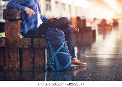 backpacker man listening to music from the phone waiting travel with train and carrying a large suitcase to the ground.