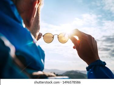 Backpacker man looking at bright sun through polarized sunglasses  enjoying mountain landscape. Eye & Vision Care human health concept image.