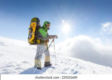 Backpacker man is posing in winter mountains