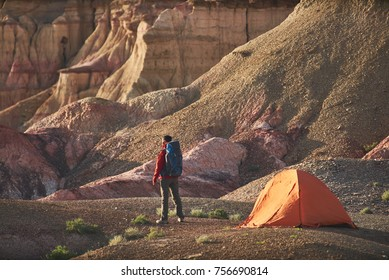 backpacker man stands near the camping orange tent and a beautiful colorful canyon in Mongolia