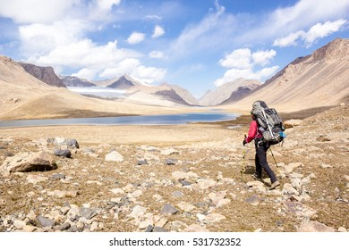 backpacker on background mountain lake, central Asia, Kyrgyzstan, Tien Shan