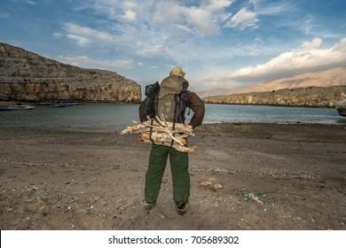 Backpacker on the beach, firewood on backpack, Oman, Arabia