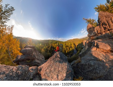 Backpacker on top of a rock fall at dawn. Wide angle aerial panorama