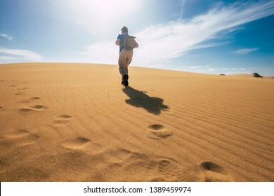 Backpacker people explore and adventure leisure activity concept with man walking on the desert dunes with backpack - alternative vacation for freedom lifestyle - scenic nature outdoor