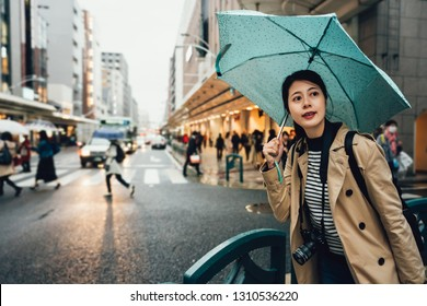 backpacker photographer holding umbrella walking in busy city urban kyoto japan in rainy day. Woman going on street during rain bad weather travel in asia. elegant tourist with camera sightseeing.