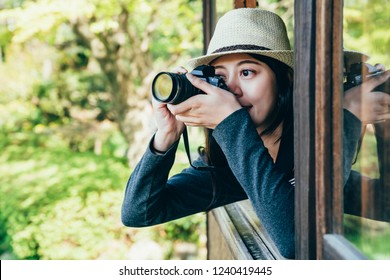 backpacker photographer zooming up the picture on camera. young girl lens man taking photo of beautiful amazing nihon teien through the window. summer view green nature.