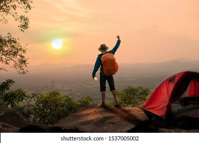Backpacker rising hand on mountain at camping site in morning