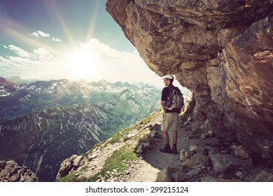 Backpacker standing in the shade under a rocky overhang looking out over the alps at the Hochvogel, Germany with a bright sunburst on the horizon