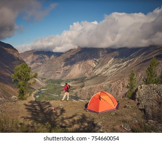 backpacker stands near the camping and look at the view valley in which there is a river or a creek and forest. the sky is cloudy, but the weather is sunny.