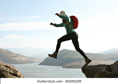 A backpacker stepping over a large gap in the mountains