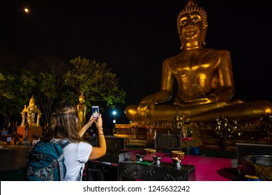 Backpacker takes a picture with smarphone. Giant Buddha Statue Pattaya City Thailand