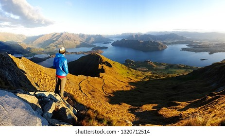 backpacker tourist man enjoying view on top of Roys Peak, mountain ovelooking lake Wanaka during sunrise in early morning, Otago region, close to Wanaka city, South Island of New Zealand