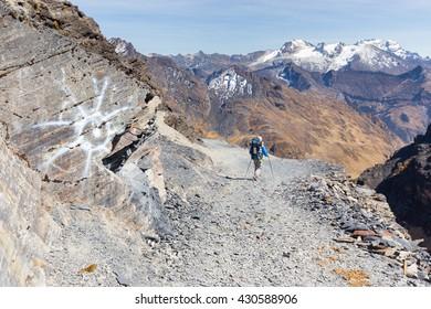 Backpacker tourist traveling walking hiking people walking mountain trail edge, El Choro trek, Cordillera real mountains canyon valley range ridge, Bolivia tourism.