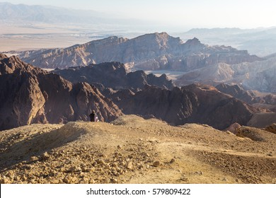 Backpacker tourist woman mountaineer sitting resting mountain cliffs edge stone desert landscape ridge view, Negev traveling destination Israel tourism.
