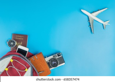 Backpacker travel accessories with plane fly pass on blue
