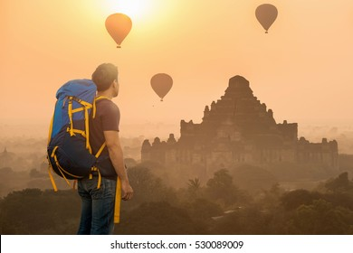 Backpacker travel at Myanmar with hot air balloons in Sunset, Sunrise