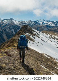 Backpacker walking along alpine ridgeline in New Zealand