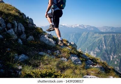 Backpacker walking up on mountain