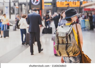 A backpacker walking in the tran station await for the train to go for journey. Travel concept.