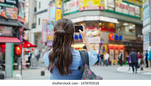 Backpacker woman visit Tokyo city, take photo on cellphone