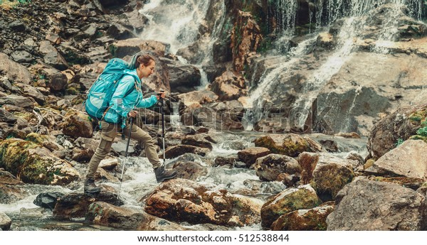 Backpacker young woman crossing mountain river with trekking poles near the waterfall