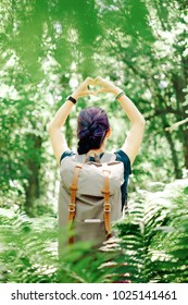 Backpacker young woman standing in summer forest and making heart shape with her hands.