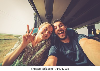Backpackers traveling around the world on the bus. Young handsome man with his girlfriend on traditional bus taking selfie on smartphone.