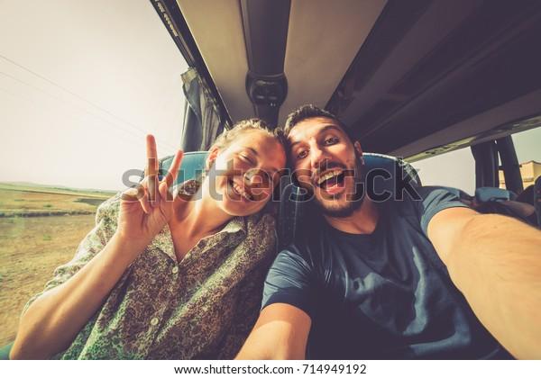 Mochileros viajando alrededor del mundo en el autobús. Joven hombre apuesto con su novia en un autobús tradicional que se toma selfie en el smartphone.