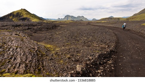 Backpackers traveling Laugavegur hiking trail. Volcanic landscape. Mountain Storkonufell at the horizon. Highlands of Iceland. Segment of the trail between Hvanngil and Emstrur
